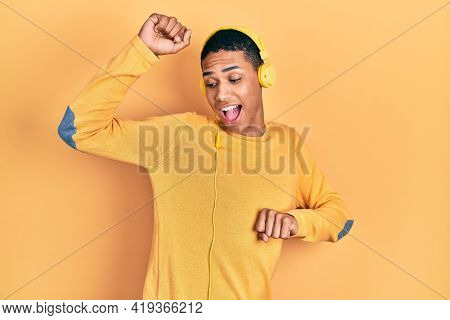 Young african american guy listening to music using headphones dancing happy and cheerful, smiling moving casual and confident listening to music