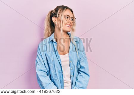 Beautiful young blonde woman wearing casual clothes and glasses looking away to side with smile on face, natural expression. laughing confident.