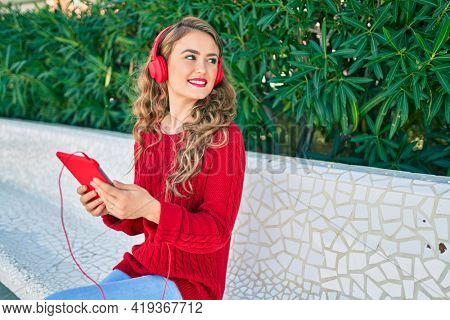 Young blonde girl smiling happy using headphones and touchpad sitting on the bench at the park.