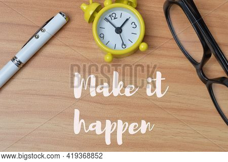 Top View Of Clock, Pen And Eyeglasses Over Wooden Background Written With Make It Happen