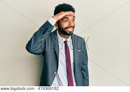 Handsome hispanic man with beard wearing business suit and tie very happy and smiling looking far away with hand over head. searching concept.