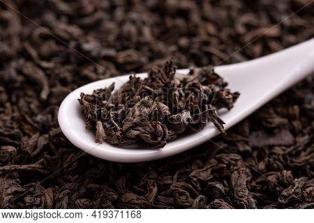 Tea Leaves Close Up. Tea In A Ceramic Spoon. A Scattering Of Tea Leaves. Black Leaf Tea Close Up.