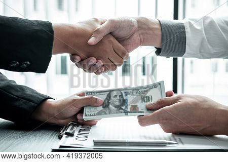 Business People Shaking Hands With Money In Hands From Their Partner To Give Success The Deal Contra