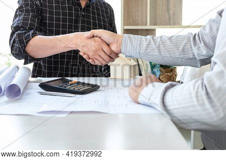Team Of Architects Or Engineering Shaking Hands While Working Cooperation On Engineer Tools And Cons