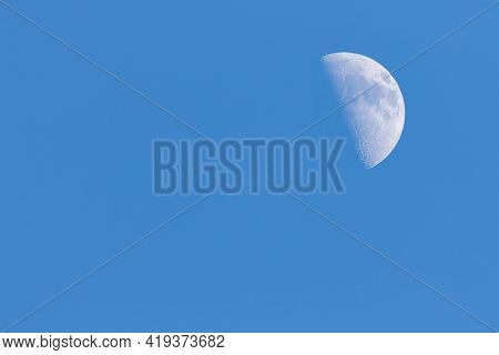 A Portrait Of A Half Moon During Day Time In A Blue Sky. The Craters On The Visible Have Of The Sate