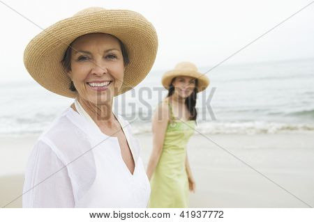 Portrait of happy senior woman and daughter walking at beach