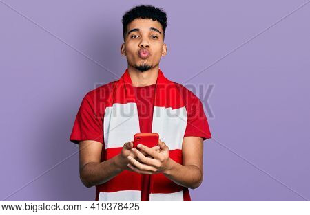 Young african american man football hooligan cheering game holding smartphone looking at the camera blowing a kiss being lovely and sexy. love expression.