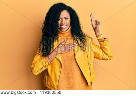 Middle age african american woman wearing wool winter sweater and leather jacket smiling swearing with hand on chest and fingers up, making a loyalty promise oath