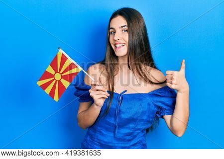 Young brunette teenager holding macedonian flag smiling happy and positive, thumb up doing excellent and approval sign