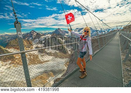 Woman With Swiss Flag On Titlis Cliff Walk Suspension Bridge. Top Of Titlis Mountain With Glacier In