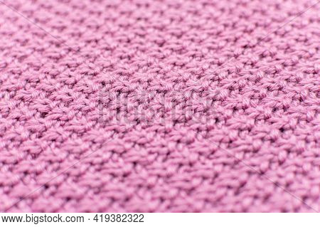 Pink Knitted Fabric Pearl Woolen Background, Close-up. The Structure Of The Fabric With A Natural Te
