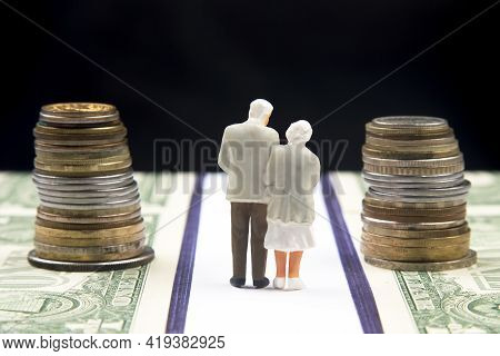 Miniature People. A Figurine Of An Elderly Pensioner Walking Along The Road Made Of Dollar Money. Pe