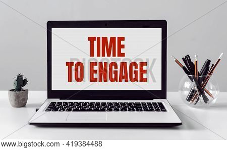 Laptop With Time To Engage Text On Modern Office Background.