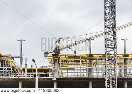 Belarus, Minsk - March 07, 2020: Industrial Tower Crane Builds New Concrete City Building Or Apartme