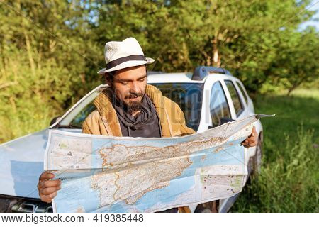 Latino Man Leaning On His 4wd Suv Car Consulting On A Map The Route Through The Forest To Follow. Lo