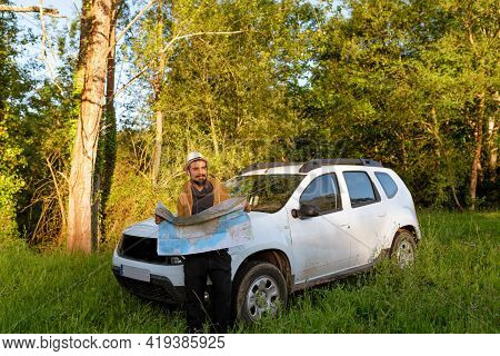 Latino Man With Hat And Map Lost In The Countryside With His 4wd Suv Car. Adventurous Person Looking