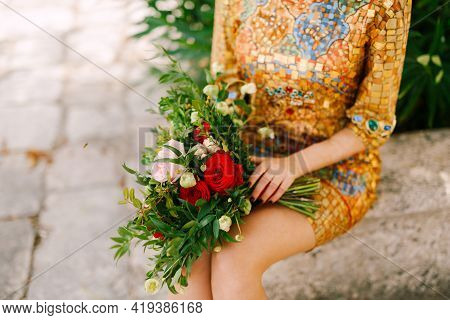 A Bride In An Unusual Golden Dress With Icon Sits And Holds A Bridal Bouquet Of White And Red Roses