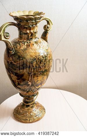 Vase. Antique, Beautiful, Enamel Stands On A Table Against The Wall. Background. Postcard