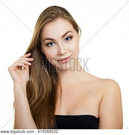 Young attractive woman with perfect make-up and long fair hair posing and smiling at studio over white background, beauty female portrait.