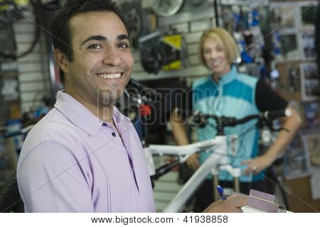 Portrait of a happy  shop keeper with cyclist in the shop