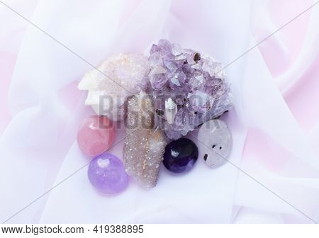 Beautiful Purple Amethyst Stones And Amethyst Quartz Crystals On A White Transparent Fabric. Cactus