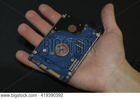 Man Hand Hold An Hdd Memory Storage Device Over Dark Surface, Tech Components, Data Security Parts