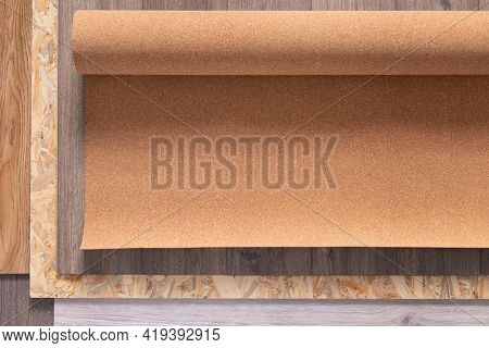 Laminate floor and cork roll on wood osb background texture. Wooden laminate floor plank with copy space