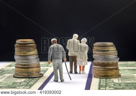 Miniature People. Elderly People, Retirees, Walk The Road Of Life Along The Money Towards The End Of