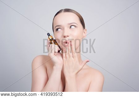 Close Up Of Pretty Brunette Lady Applying Cosmetic Oil On Her Face With Pipette. Beauty Therapy Conc
