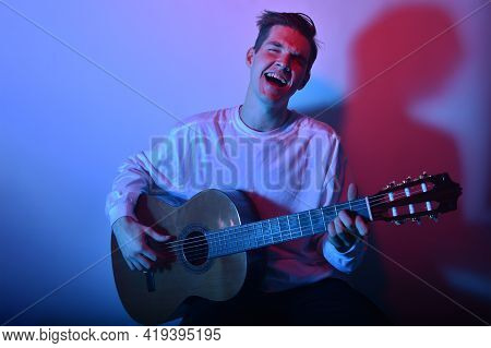 A Man Plays An Acoustic Guitar In Neon Red-blue Light. A Man Learns To Play The Guitar, Music, Hobbi