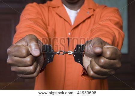 Meio das mãos do prisioneiro restringida com algemas