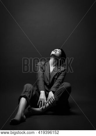 Young Pretty Short Haired Brunette Woman In Business Smart Casual Suit Barefoot Sitting On Floor Loo