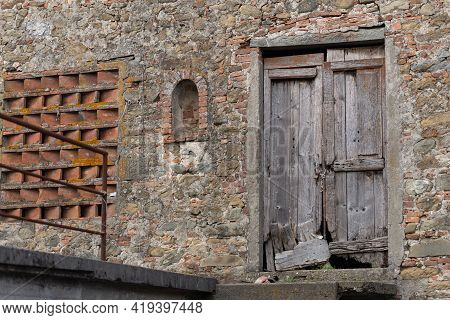 The Wall Of An Old Stone Barn. An Old And Decayed Wooden Door In An Old Barn In Tuscany.