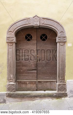 Beautiful Front Door. A Very Old Door To One Of The Thousand-year-old Houses In Barga. Door With Rou