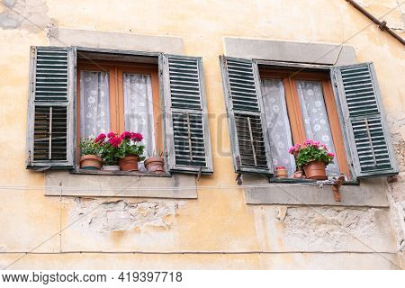 Old Windows In A Medieval Town. Windows With Street Sills With Flowers On Them. The Old Italian Shut