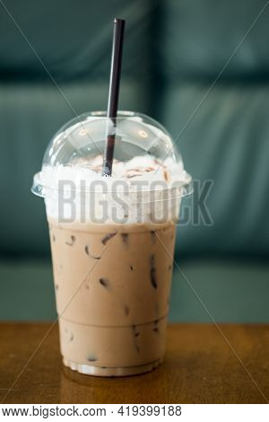 Iced Coffee Mocha With Milk In Plastic Glass On The Wood Table In Cafe With Gray Sofa Background