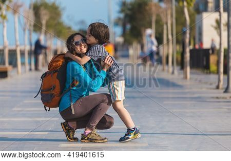 The Boy Hugs His Mother, The Child Walks With His Mother Along The City Street, The Woman Hugs Her S