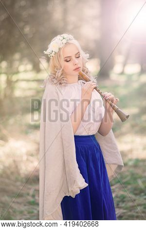 Minsk, Belarus - 04.14.2020. Beautiful Blonde Female In Slavic Clothes Playing The Flute And Pipe In