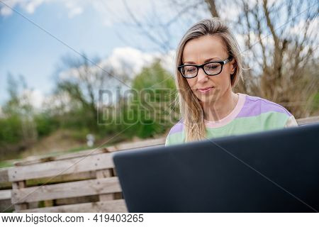 Woman With Glasses Working Outside Using A Laptop. Working Outside The Office.