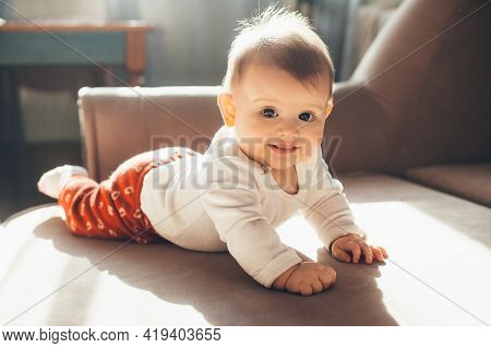 Adorable Girl Posing And Smiling At Camera On The Couch In A Sunny Day At Home