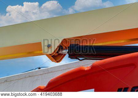 Closeup Hydraulic Of Boom Lift. Orange Articulated Boom Lift. Maintenance And Repair Hydraulic Boom