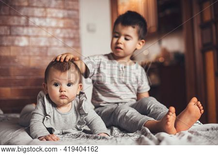 Brother And Newborn Sister Sitting On The Couch Together And Playing