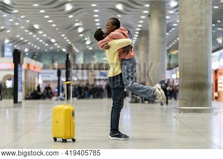 Happy Meeting Of Loving Couple After Long Time. African Man And Woman Excited Hugging In Airport Ter