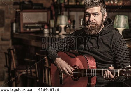 Bearded Guitarist Plays. Bearded Man Playing Guitar, Holding An Acoustic Guitar In His Hands. Play T