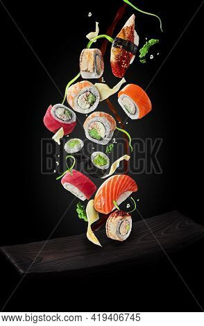 Sushi With Garnishes And Soy Sauce Hovering Over Plate On Black Background