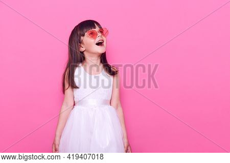 Cute Little Girl Wearing Fashionable Glasses In Heart Shape And White Dress, Having Excited Facial E