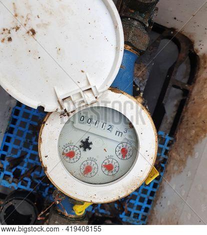Water Meter. Outdoor Rusty And Dirty Water Meter For Measuring The Water Flow. Top View Of Water Met