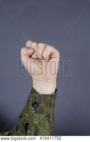 Hand In Camouflage Shows Gesture With His Fingers On Gray Background. Fingers Clenched Into A Fist.