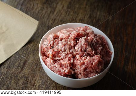 White Ceramic Bowl With Raw Minced Meat On A Dark Wooden Table. A Full Bowl Of Minced Pork And Beef.