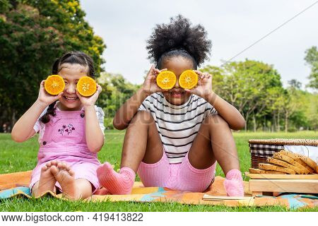 Two African American Little Girl Sitting On The Mat And Eating Oranges Fruits In The Autumn Park , P
